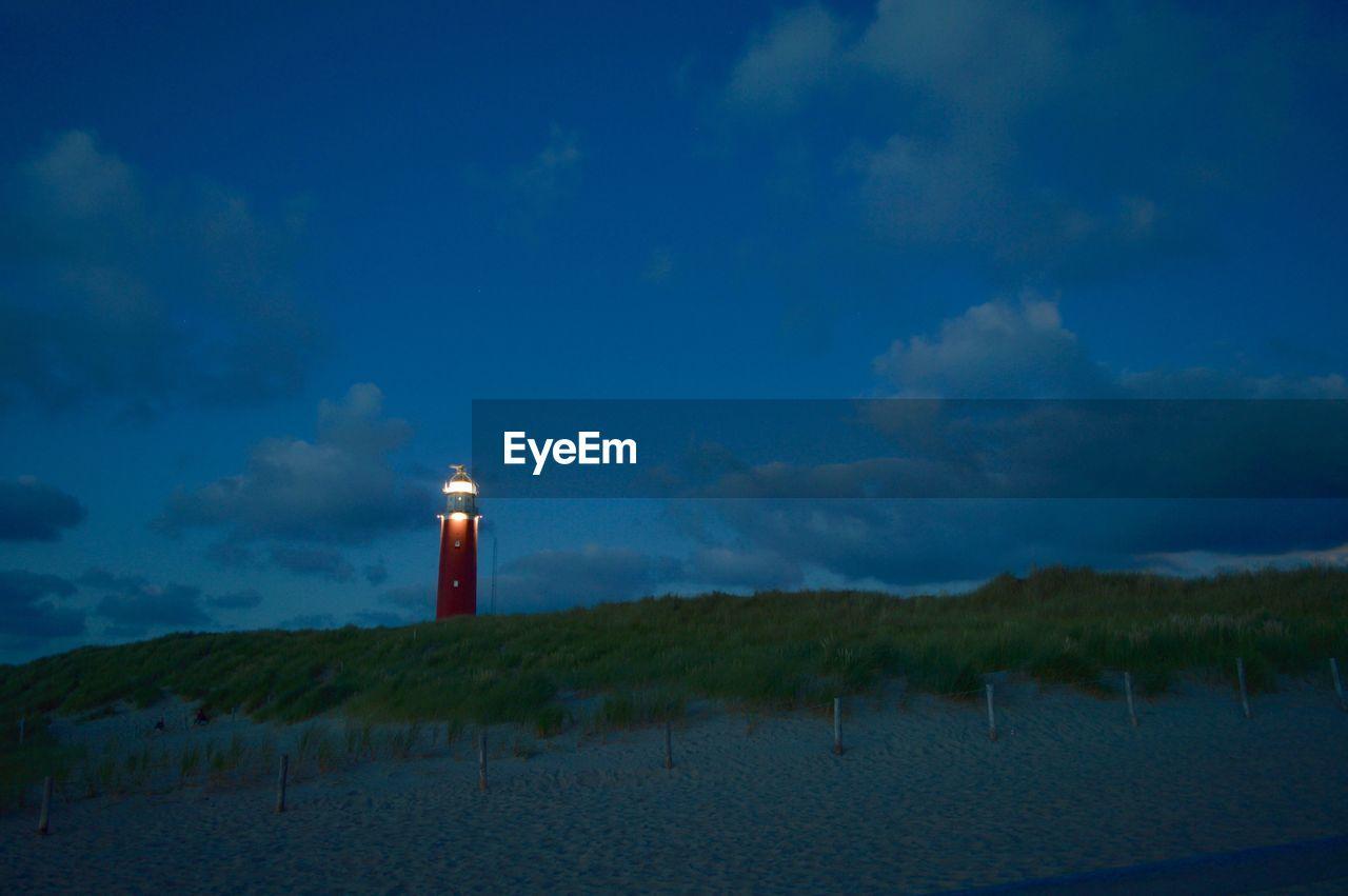 Illuminated Lighthouse At Beach Against Sky