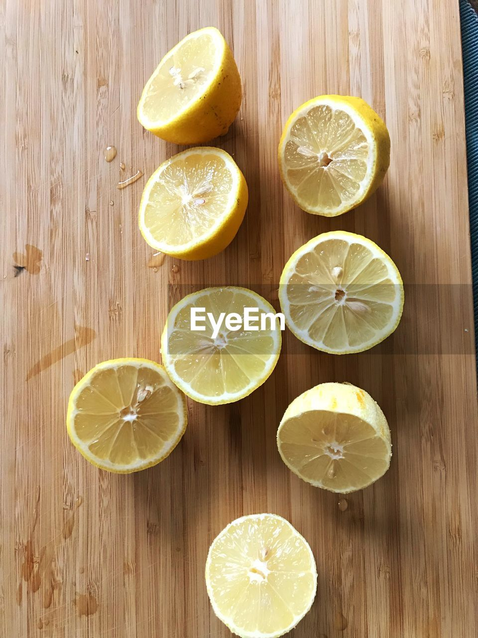 citrus fruit, food and drink, fruit, food, slice, healthy eating, freshness, lemon, wellbeing, table, wood - material, no people, still life, indoors, lime, yellow, directly above, high angle view, cross section, close-up, orange, sour taste