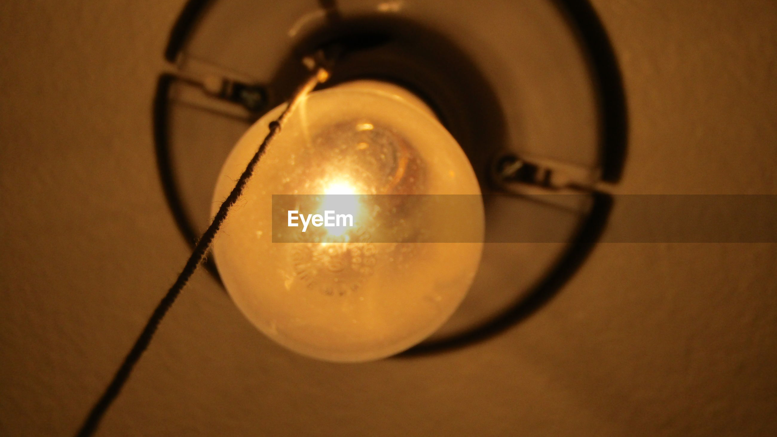 Low angle view of illuminated light bulb on ceiling