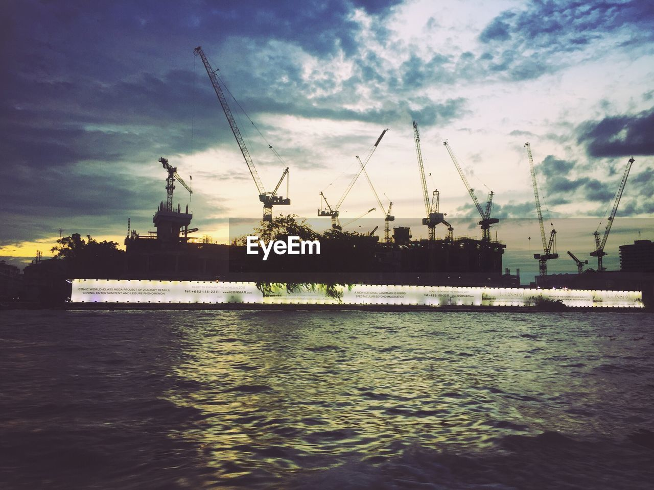 sky, water, waterfront, cloud - sky, outdoors, no people, built structure, architecture, crane - construction machinery, building exterior, river, crane, harbor, day, silhouette, commercial dock, travel destinations, nature, industry, nautical vessel, city, drilling rig