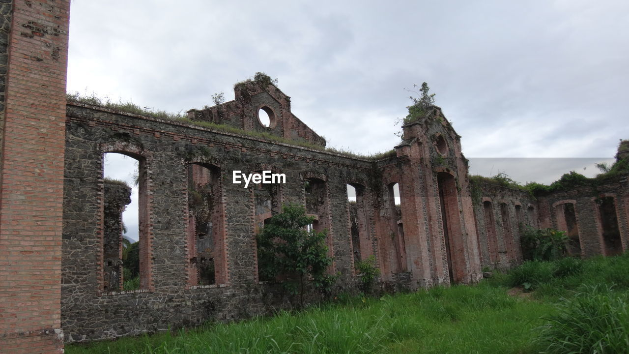 old ruin, architecture, abandoned, damaged, old, history, built structure, cloud - sky, sky, building exterior, run-down, window, low angle view, no people, ancient, day, bad condition, grass, outdoors, ancient civilization