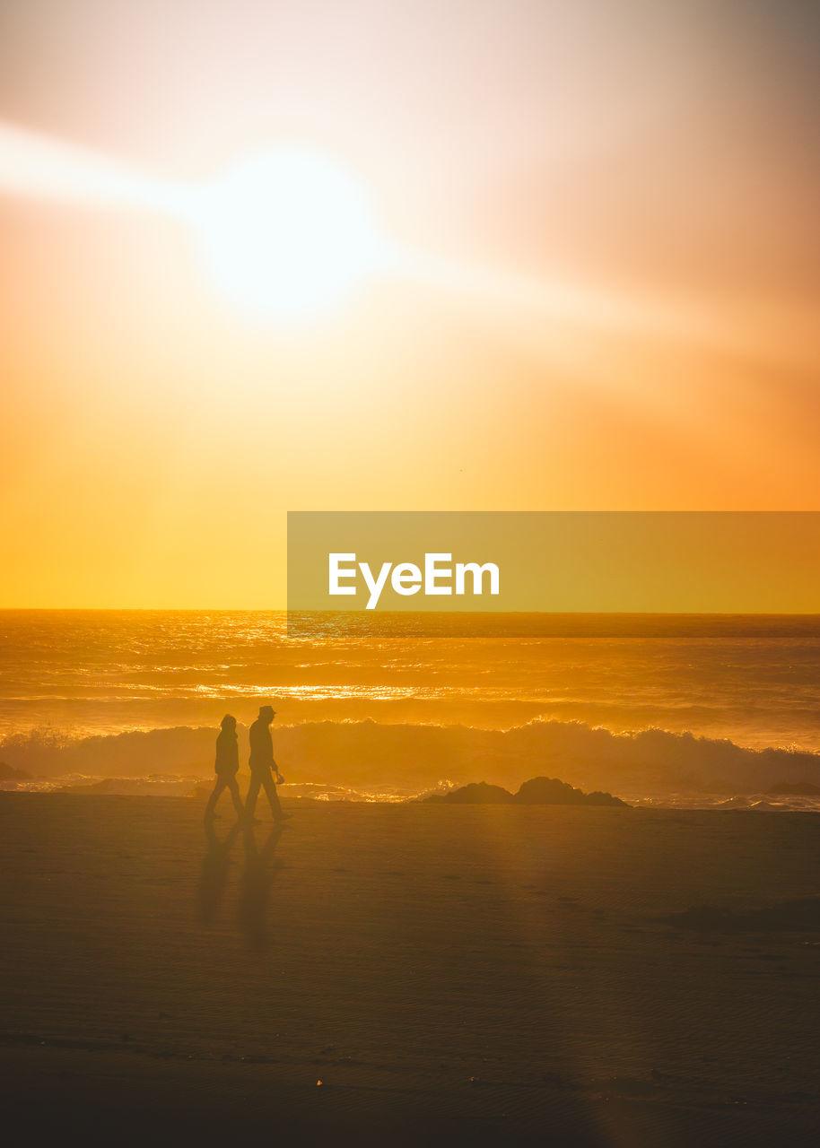 Silhouette Couple Walking At Beach Against Orange Sky