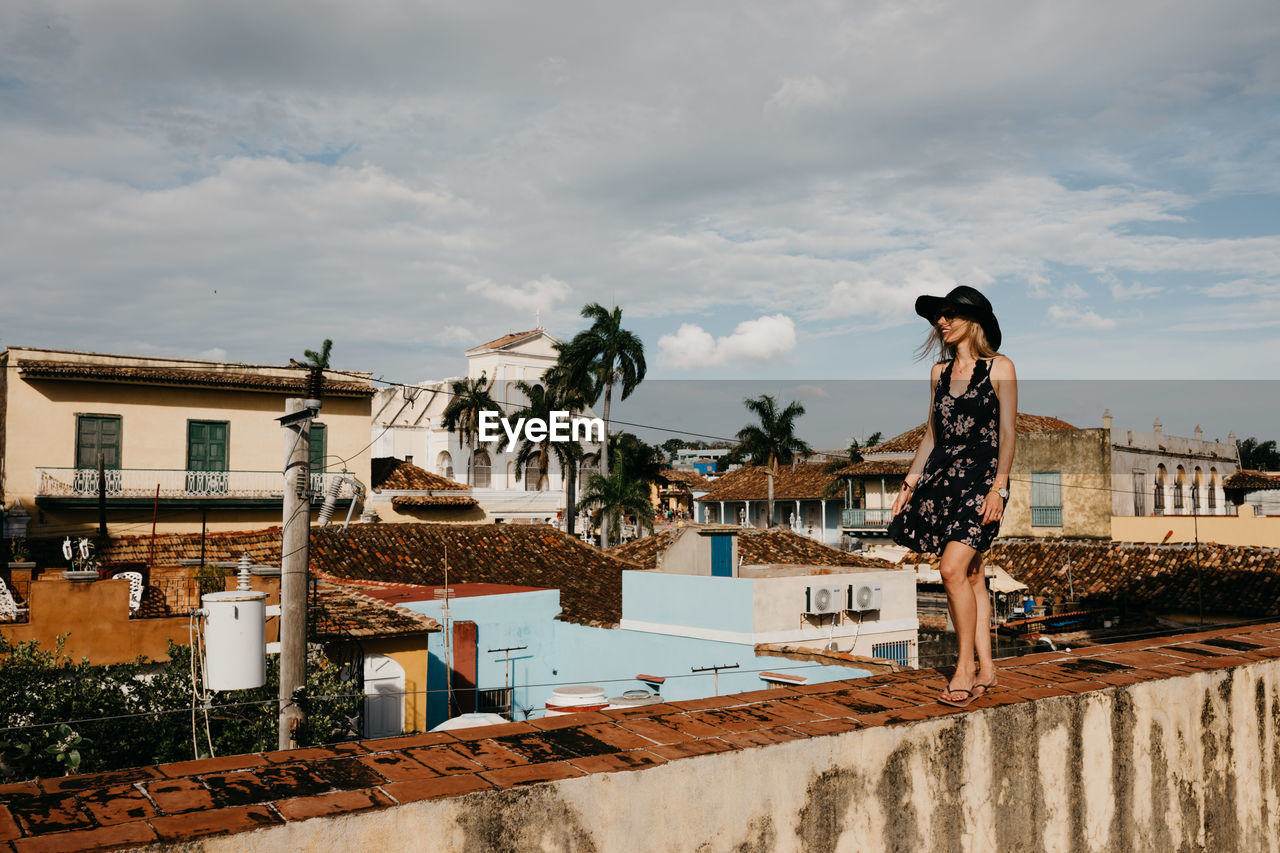 Smiling Young Woman Standing On Wall Against Cloudy Sky