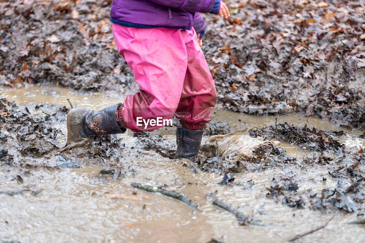 pink color, one person, water, day, low section, human body part, nature, wet, child, offspring, human leg, puddle, childhood, body part, standing, rubber boot, unhygienic, outdoors, dirt, dirty, pollution, mud, human limb