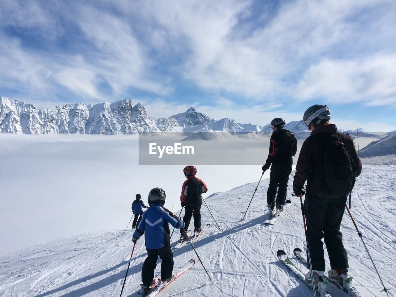 Rear View Of People Skiing On Snowcapped Mountains Against Sky