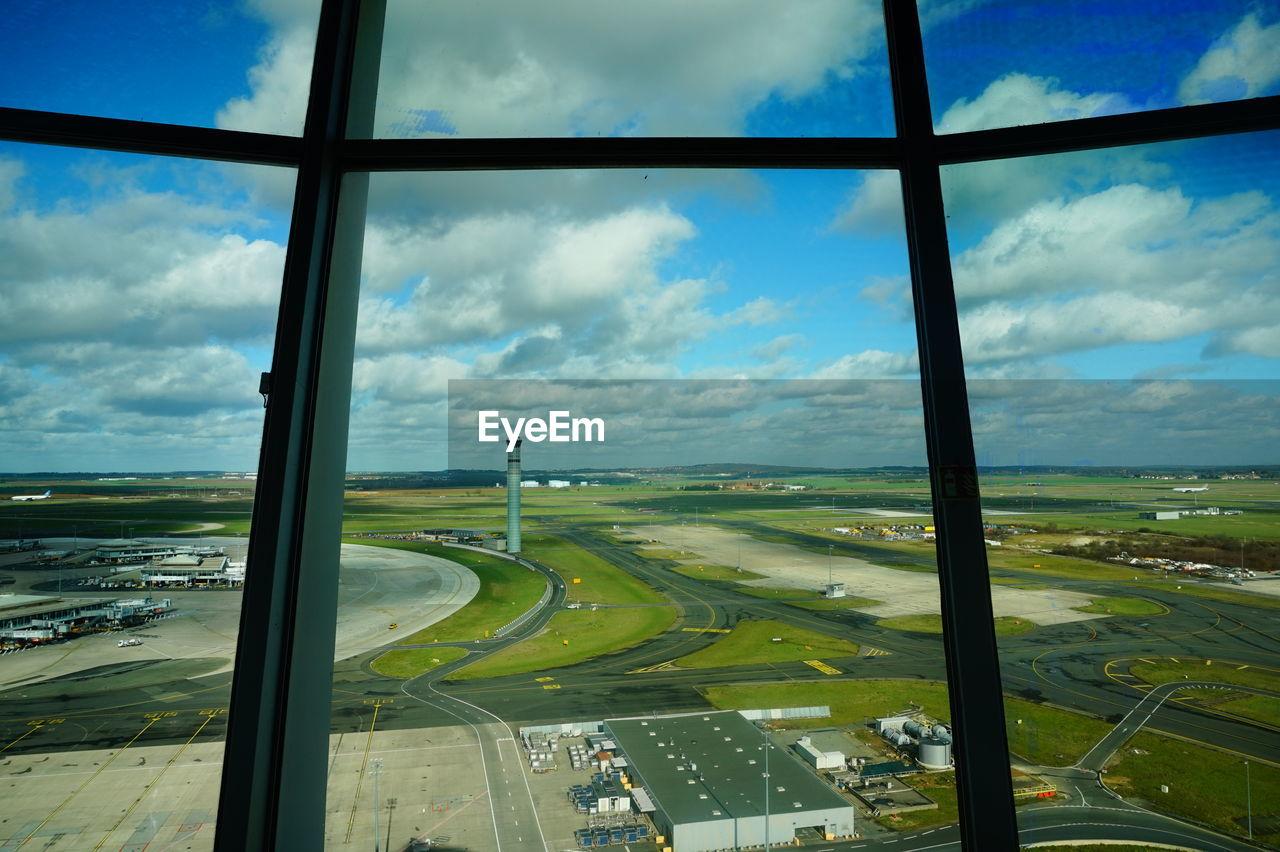 Airport runway seen through glass window