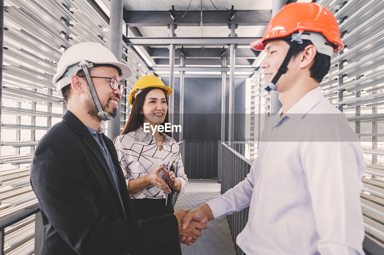 headwear, occupation, helmet, hat, smiling, women, adult, hardhat, real people, young adult, waist up, business, cooperation, group of people, mid adult, working, men, females, standing, teamwork, coworker, design professional