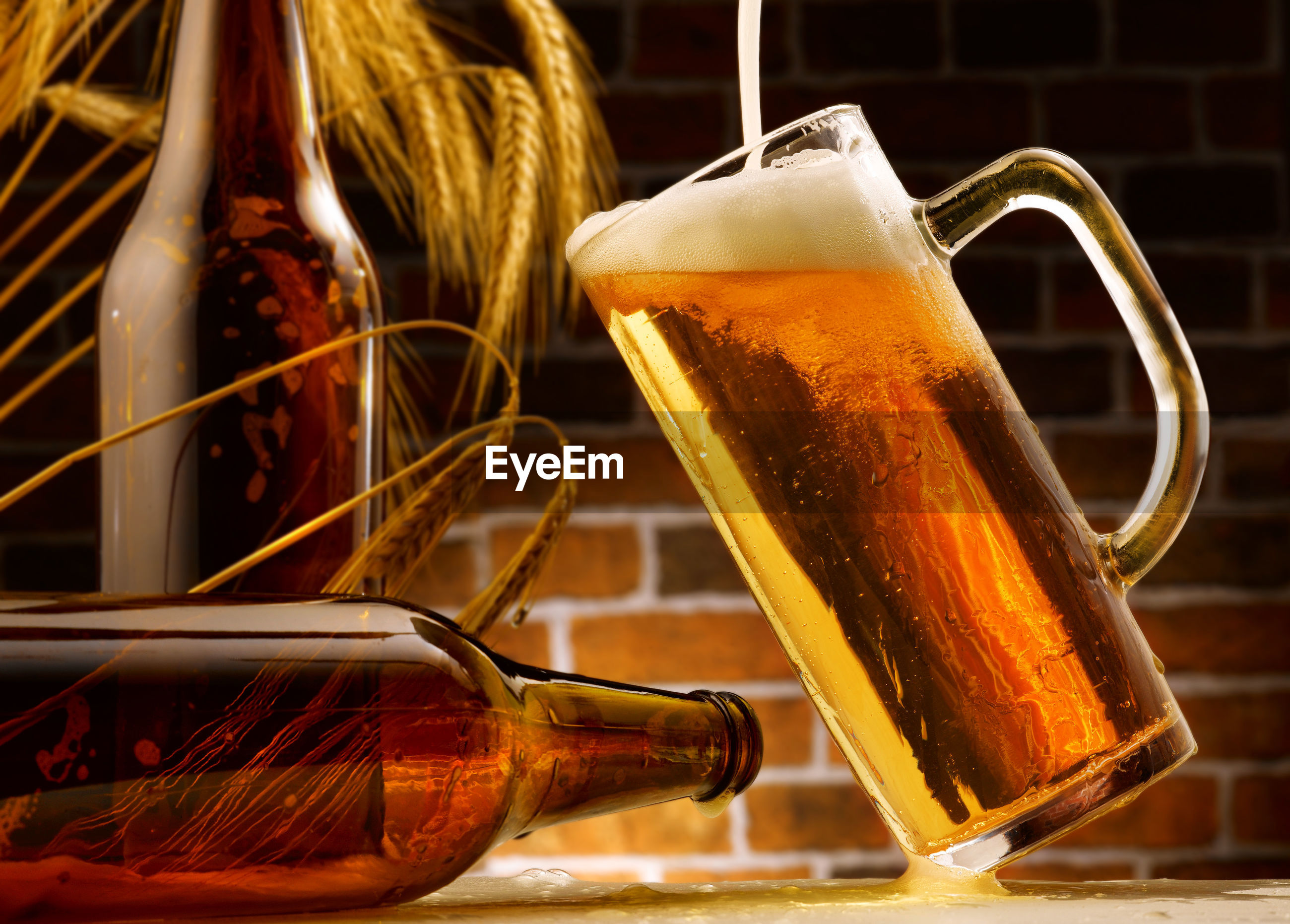 CLOSE-UP OF BEER GLASS ON TABLE AGAINST BRIGHT LIGHT