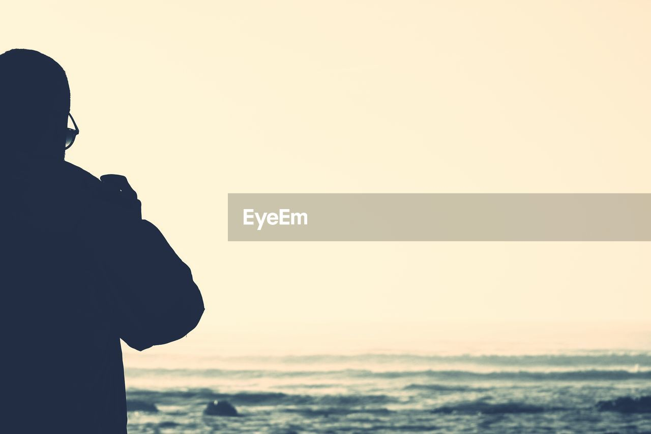 Man Looking At Sea Against Clear Sky