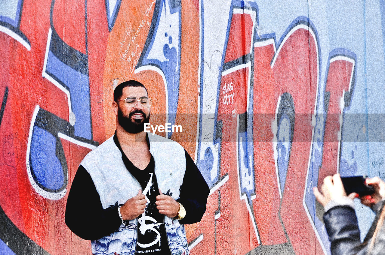 real people, graffiti, one person, outdoors, street art, standing, front view, day, leisure activity, casual clothing, young men, lifestyles, holding, smiling, architecture, built structure, young adult, looking at camera, men, building exterior, portrait, people