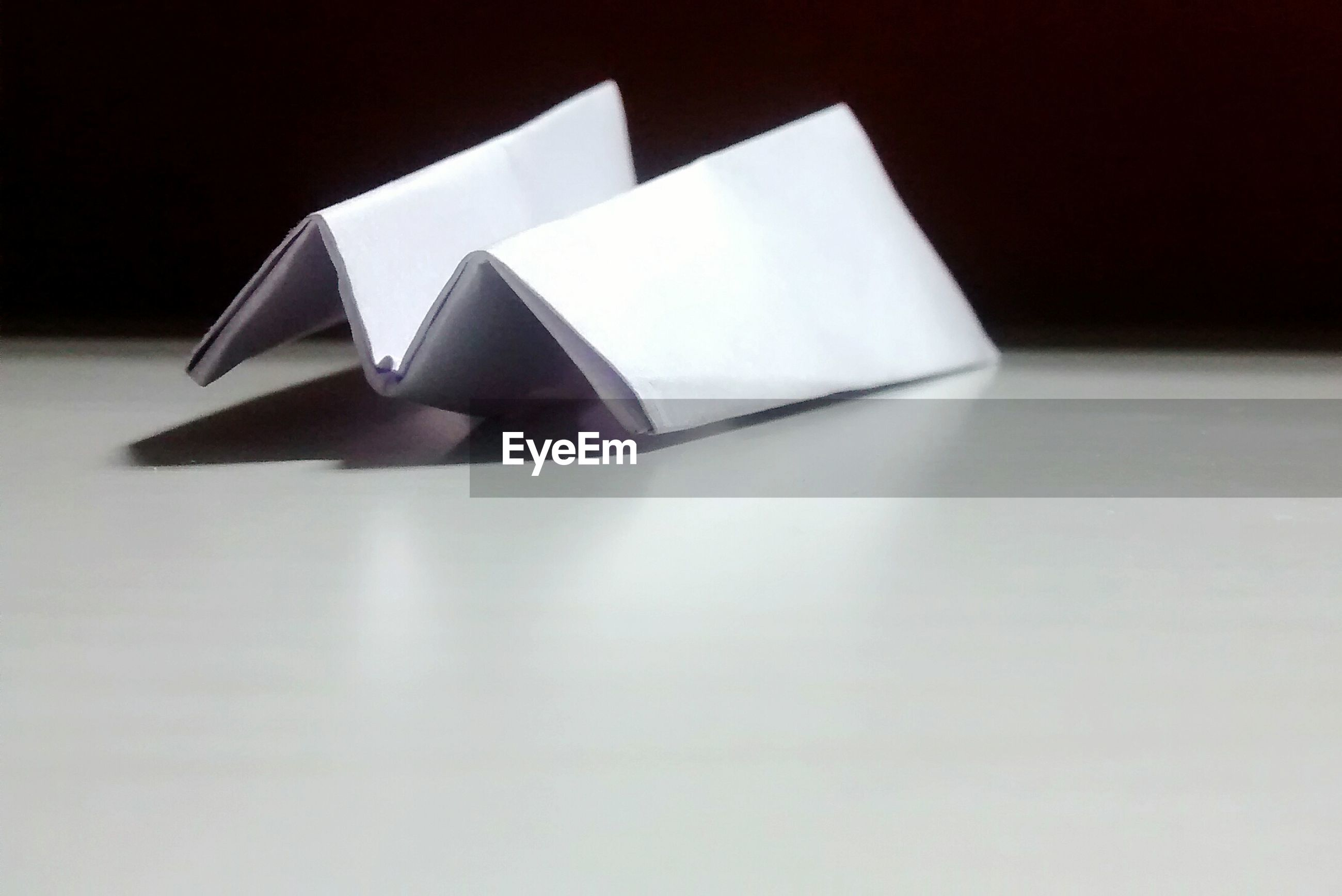 Paper airplane on table against wall
