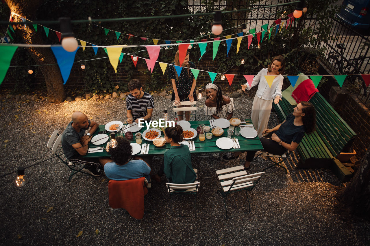group of people, sitting, crowd, large group of people, real people, men, seat, adult, women, food and drink, chair, young adult, table, young women, leisure activity, high angle view, friendship, casual clothing, nature, outdoors