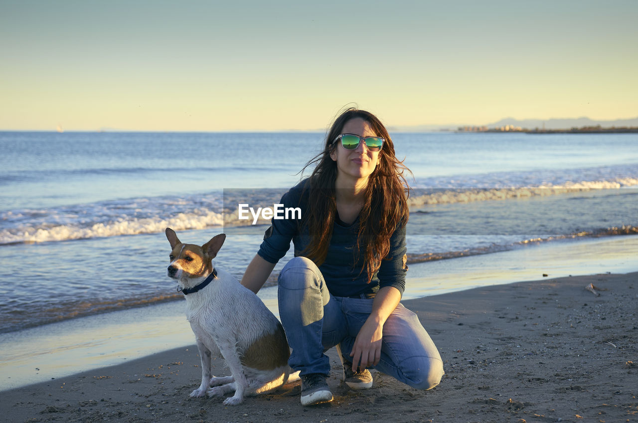 Young Woman Playing With Dog At Beach During Sunset