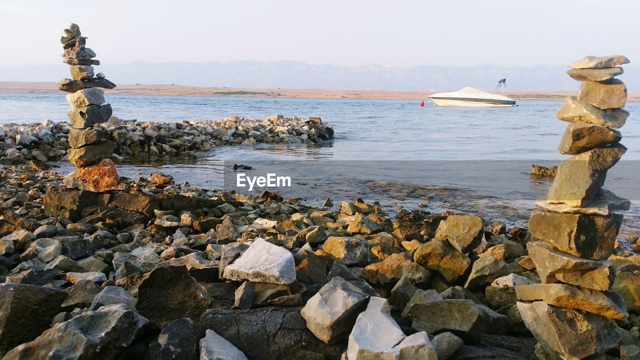 water, sea, rock - object, nature, day, scenics, beauty in nature, outdoors, clear sky, beach, groyne, sky, no people, horizon over water