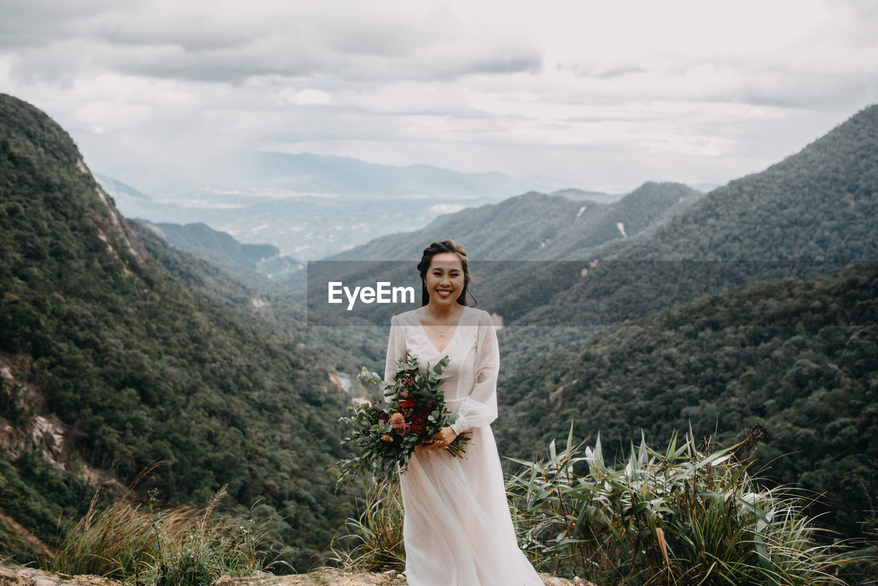 mountain, wedding, nature, celebration, bride, beauty in nature, women, young adult, newlywed, adult, wedding dress, smiling, sky, scenics - nature, one person, plant, standing, cloud - sky, flower arrangement, lifestyles, bouquet, mountain range, outdoors
