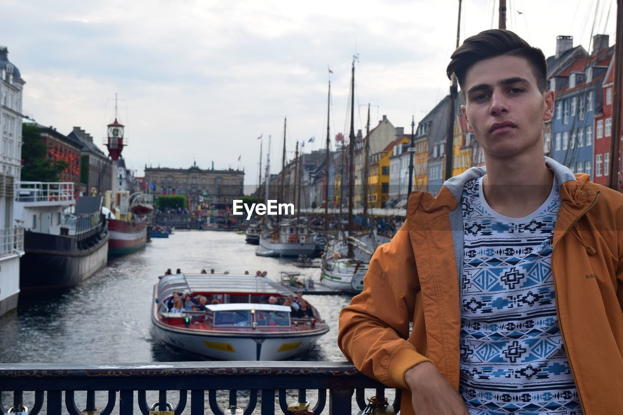 Young man standing at harbor against sky in city