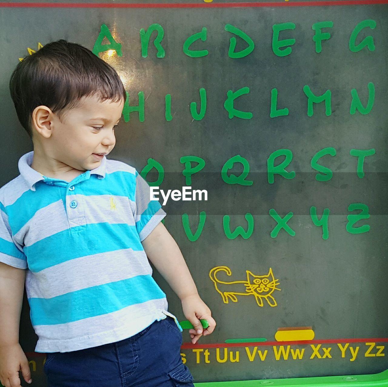 Boy standing against alphabets on blackboard
