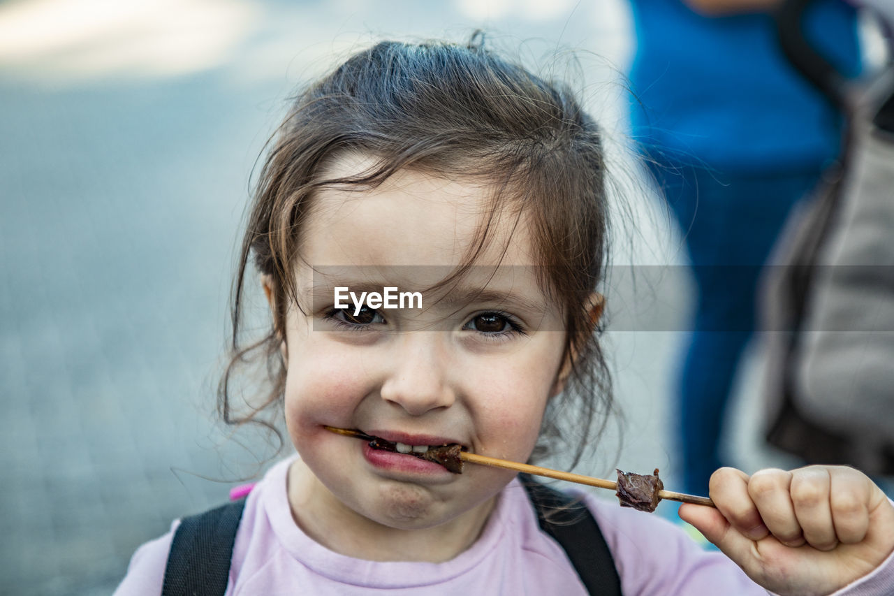 Close-up portrait of girl eating food outdoors
