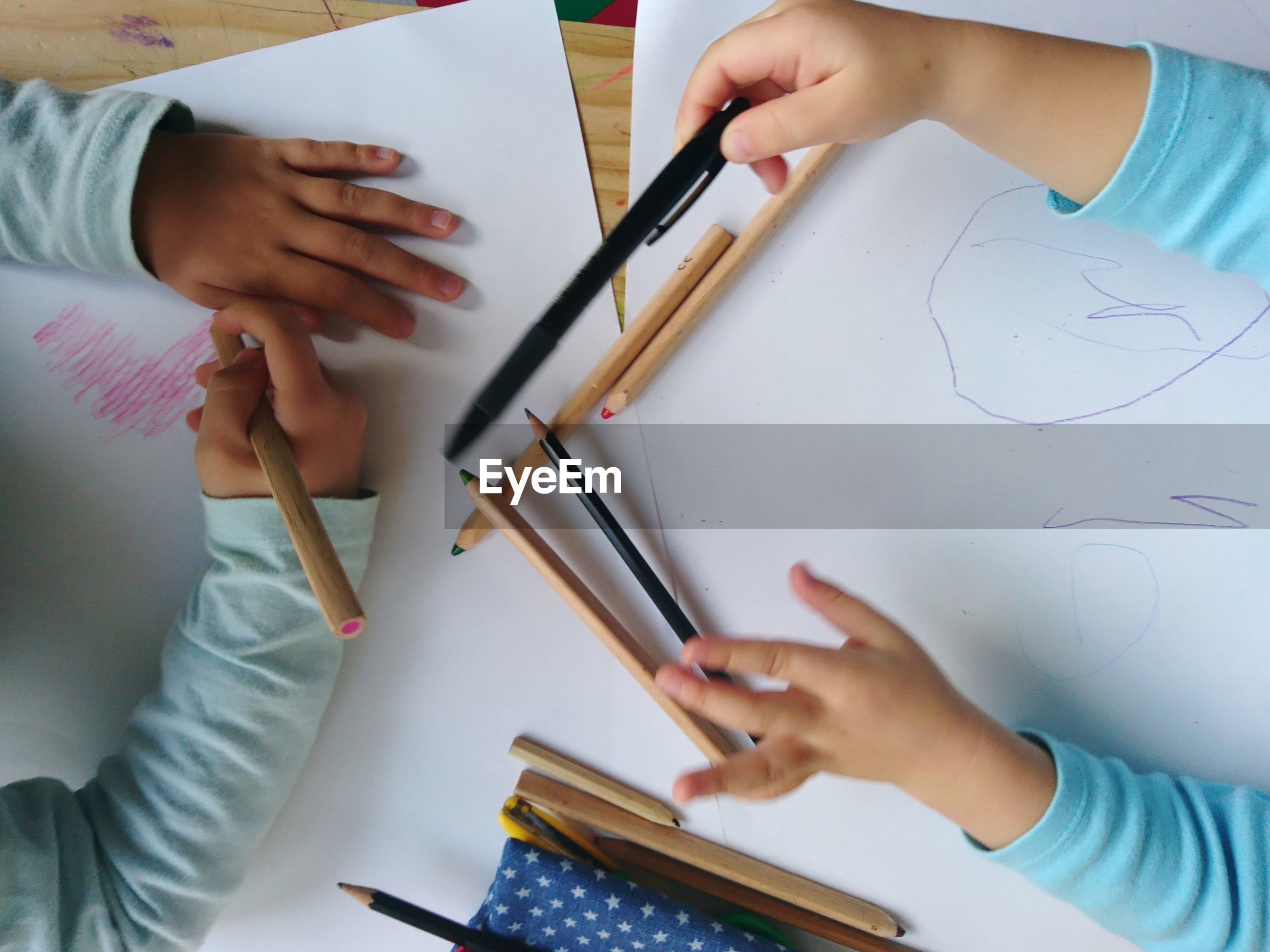 Cropped hands of children drawing on cardboard