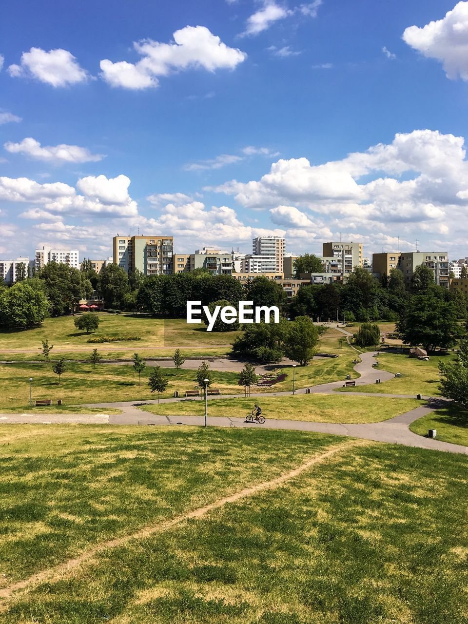 sky, grass, architecture, growth, built structure, cloud - sky, sunlight, no people, building exterior, day, green color, tree, outdoors, nature, city, skyscraper, scenics, beauty in nature, golf course