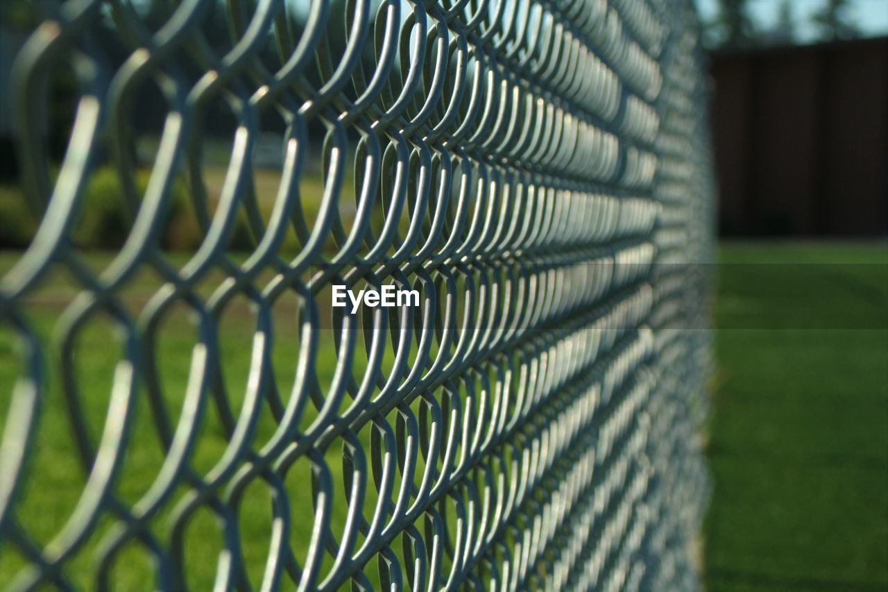 fence, pattern, close-up, no people, boundary, barrier, focus on foreground, metal, safety, day, security, green color, protection, selective focus, chainlink fence, outdoors, nature, design, grass, wire, steel
