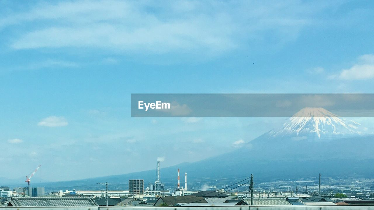 cloud - sky, sky, mountain, transportation, architecture, no people, industry, water, day, built structure, nature, outdoors, machinery, pier, smoke - physical structure, crane - construction machinery, sea, commercial dock, building exterior, construction industry, snowcapped mountain