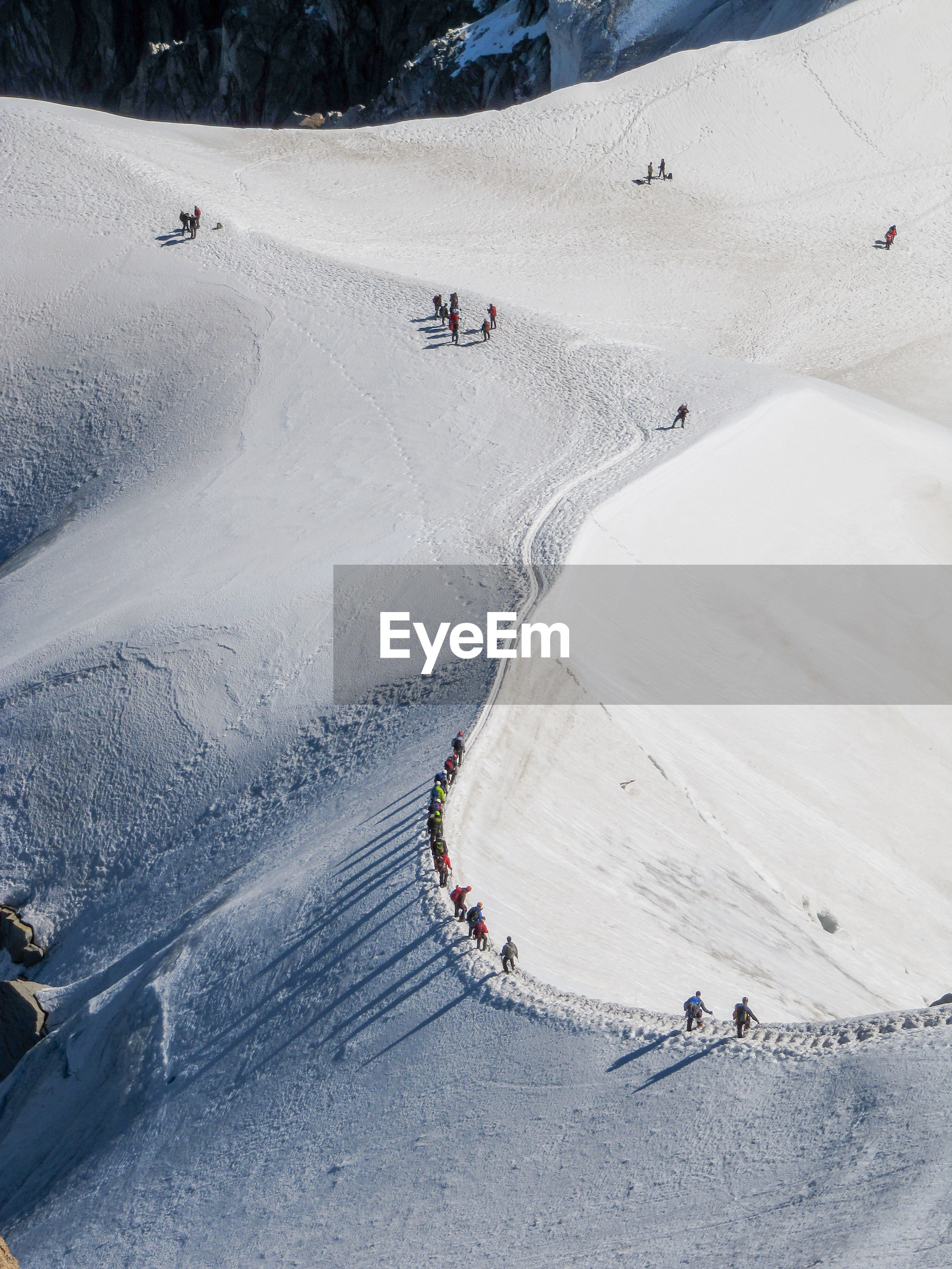 People skiing on snow covered landscape against cloudy sky