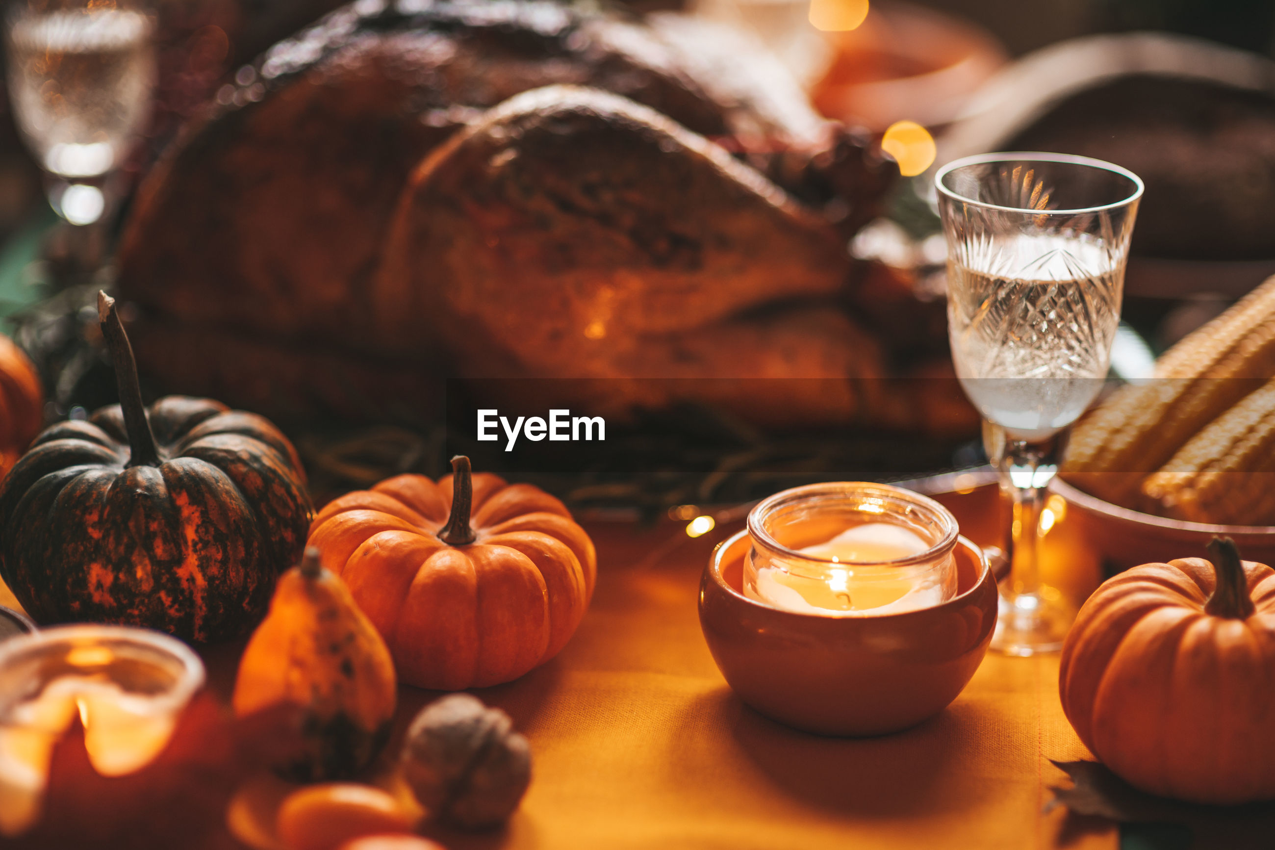 CLOSE-UP OF PUMPKIN AND WINE ON TABLE