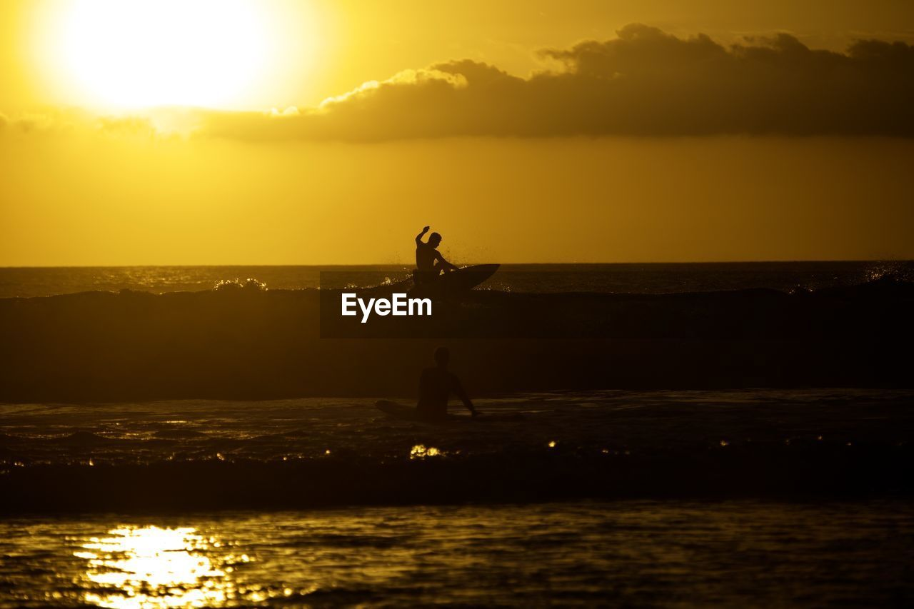 sunset, sky, water, silhouette, real people, orange color, scenics - nature, beauty in nature, lifestyles, sea, nature, waterfront, one person, standing, sunlight, leisure activity, men, sun, outdoors, freedom, horizon over water, human arm, arms raised