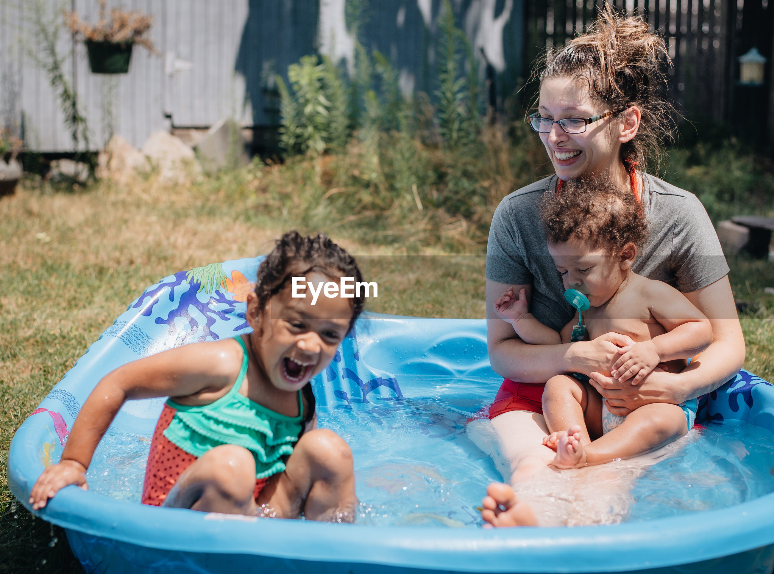Cheerful mother with kids relaxing in wading pool