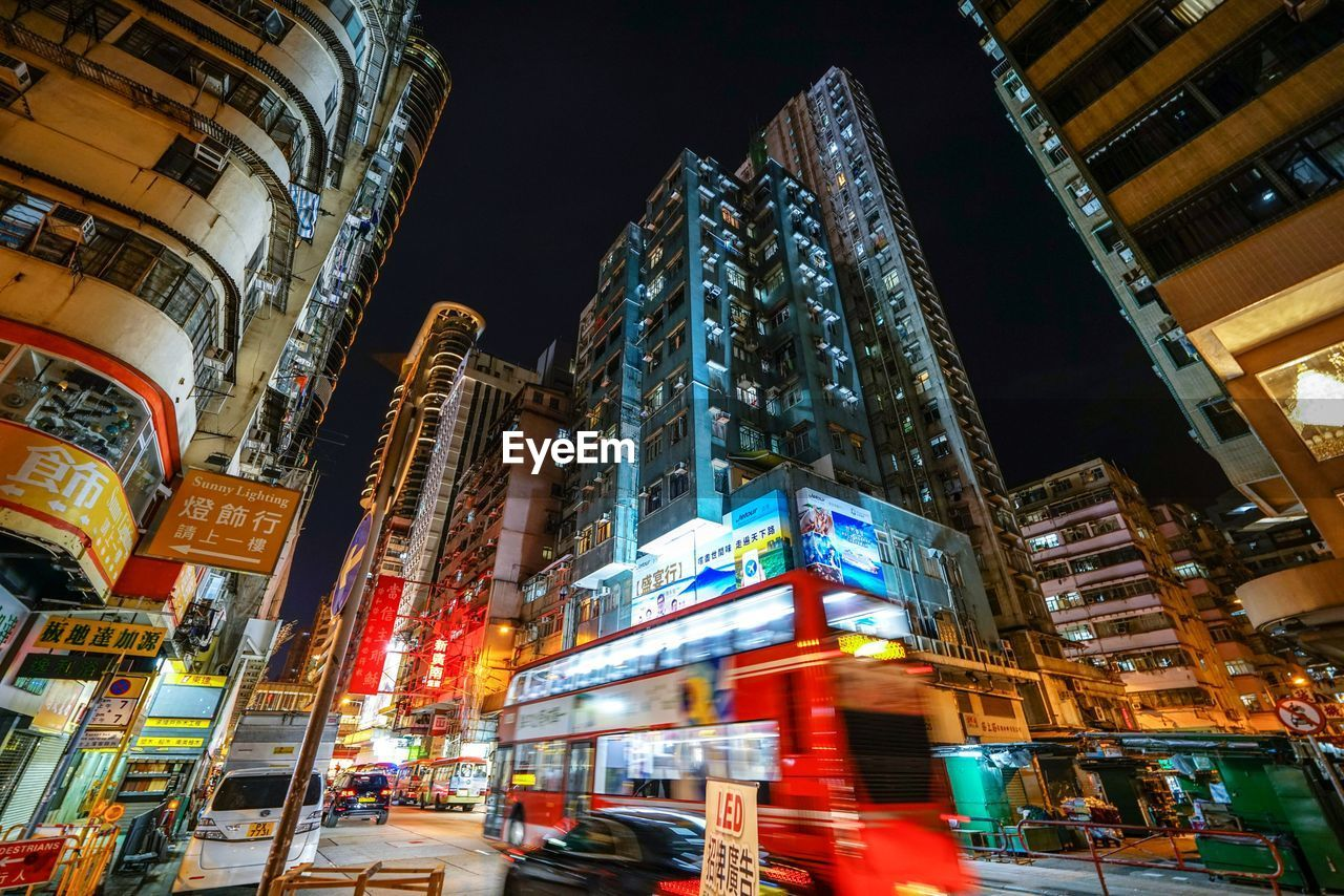 building exterior, illuminated, architecture, city, night, built structure, transportation, city life, mode of transportation, street, city street, motion, building, incidental people, low angle view, tall - high, land vehicle, blurred motion, text, communication, office building exterior, modern, cityscape, skyscraper