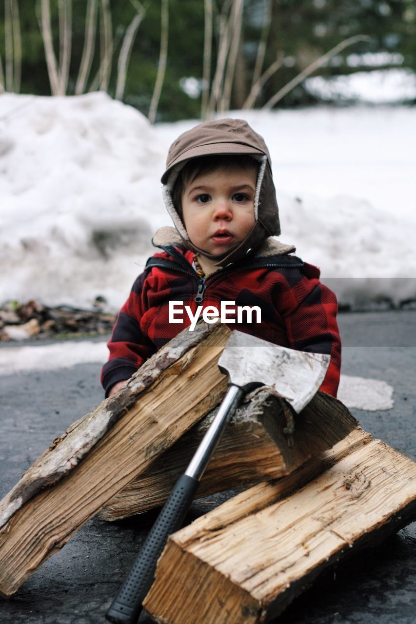 Close-up of cute toddler behind firewood