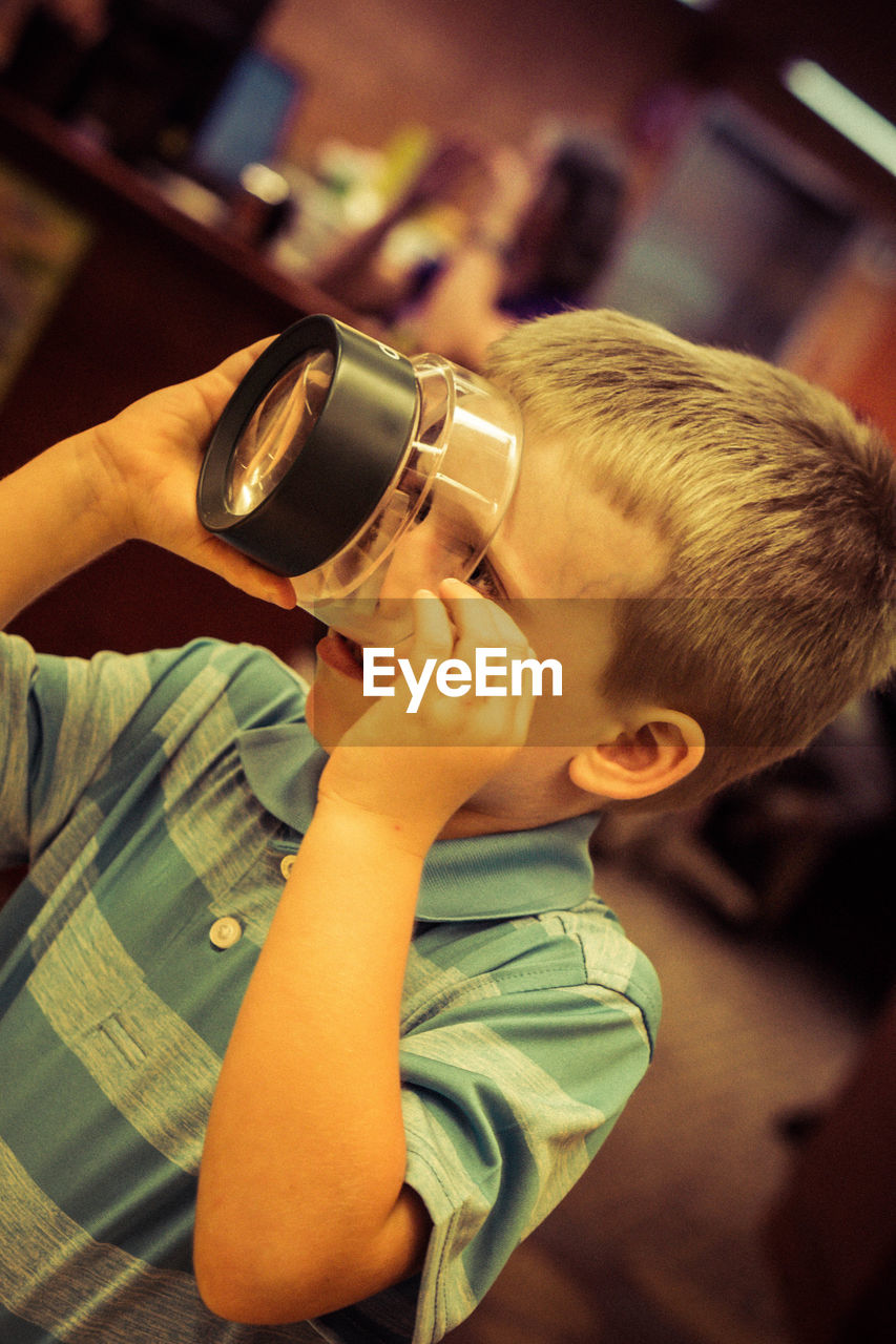 Close-up of boy using old-fashioned magnifying glass