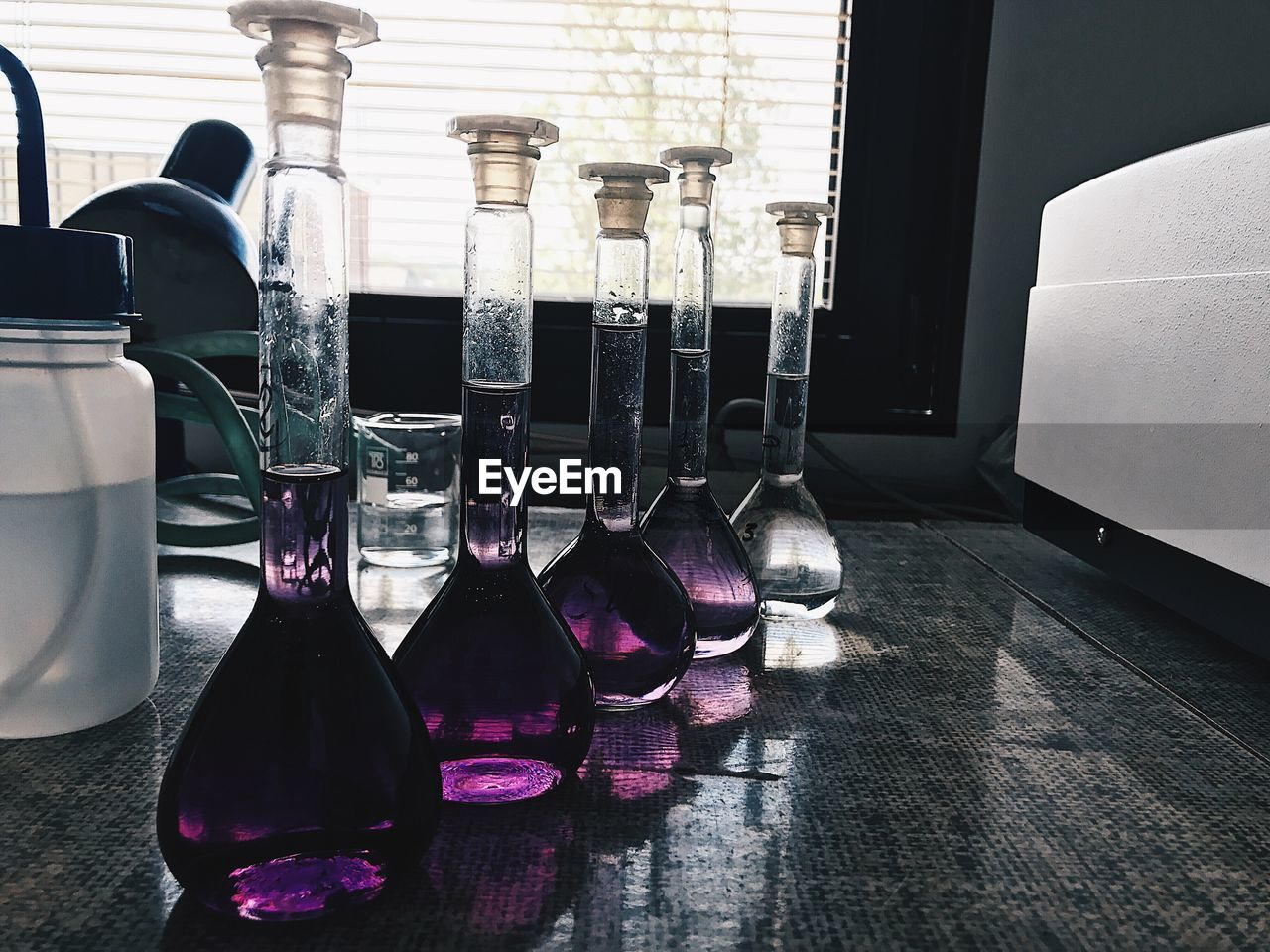 CLOSE-UP OF BOTTLES ON TABLE IN WINDOW