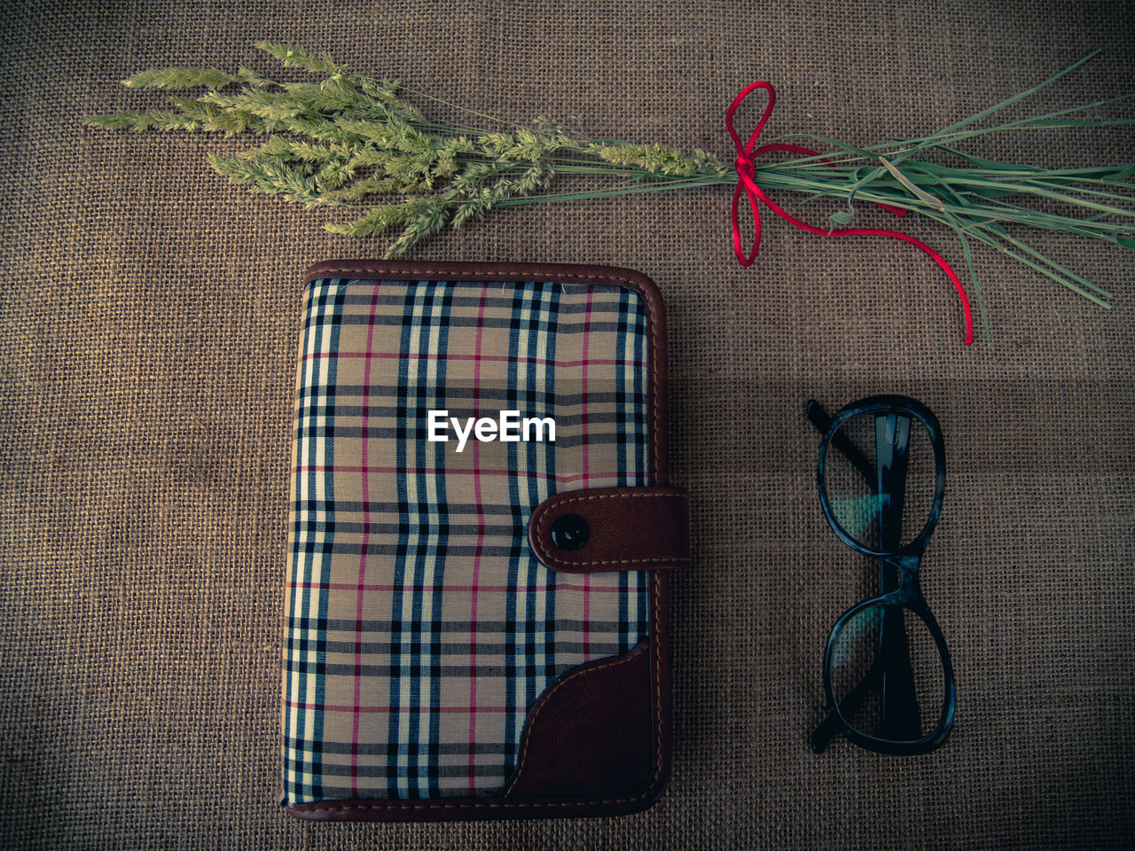 Directly above shot of diary and eyeglasses with plants on burlap