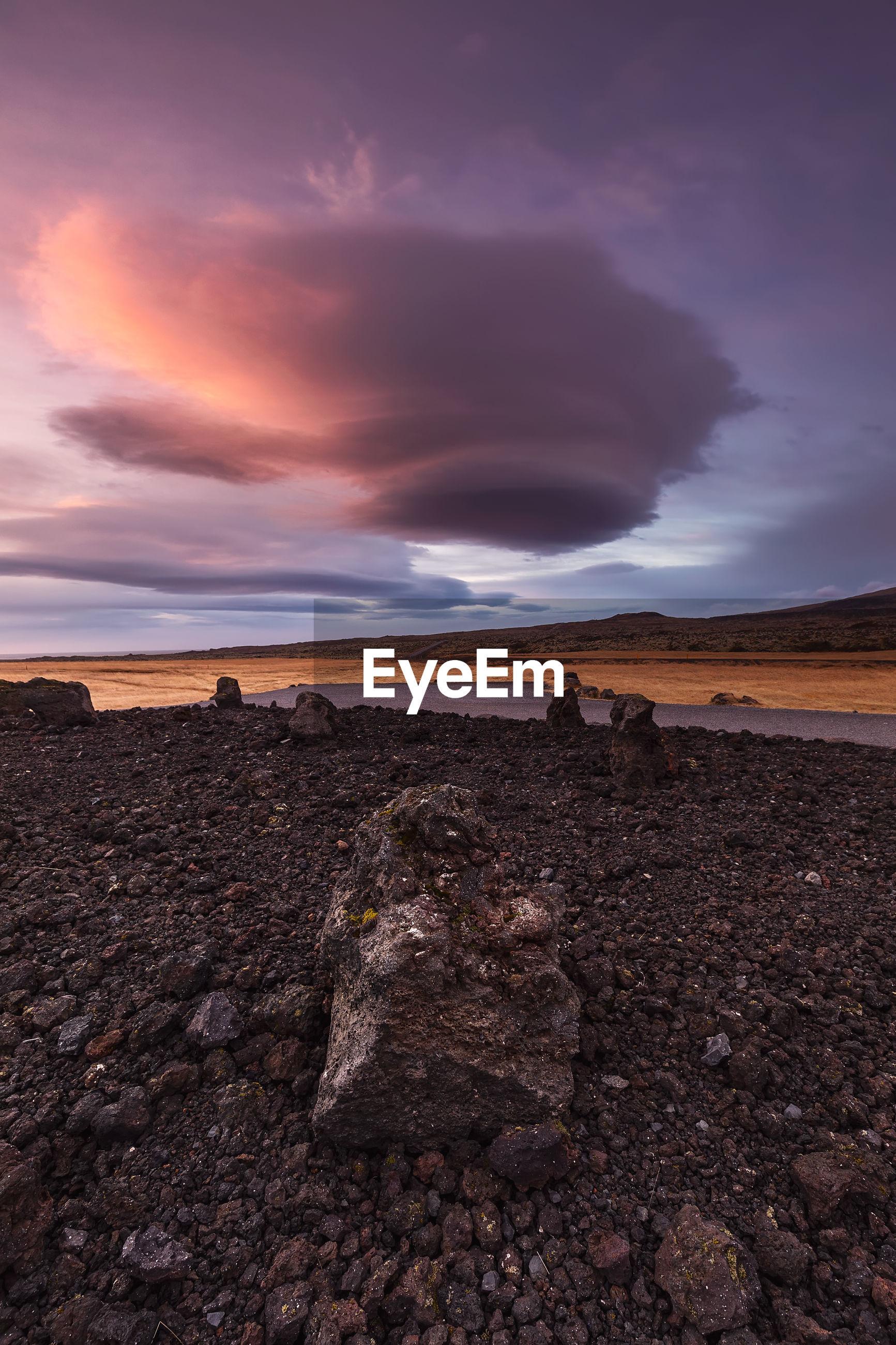 Rocks on land against sky during sunset