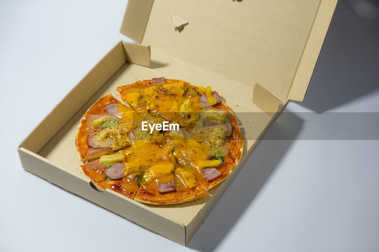 HIGH ANGLE VIEW OF PIZZA IN BOX ON TABLE