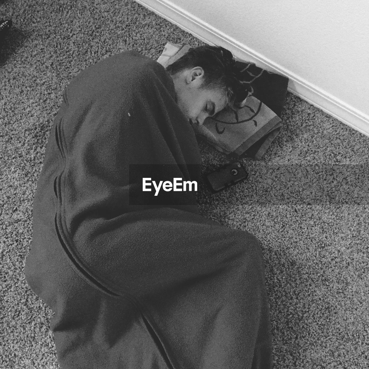 High Angle View Of Young Man Sleeping On Rug At Home