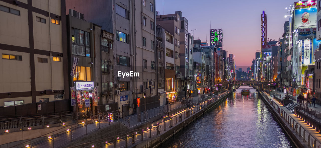 Canal Amidst Illuminated Buildings In City During Sunset