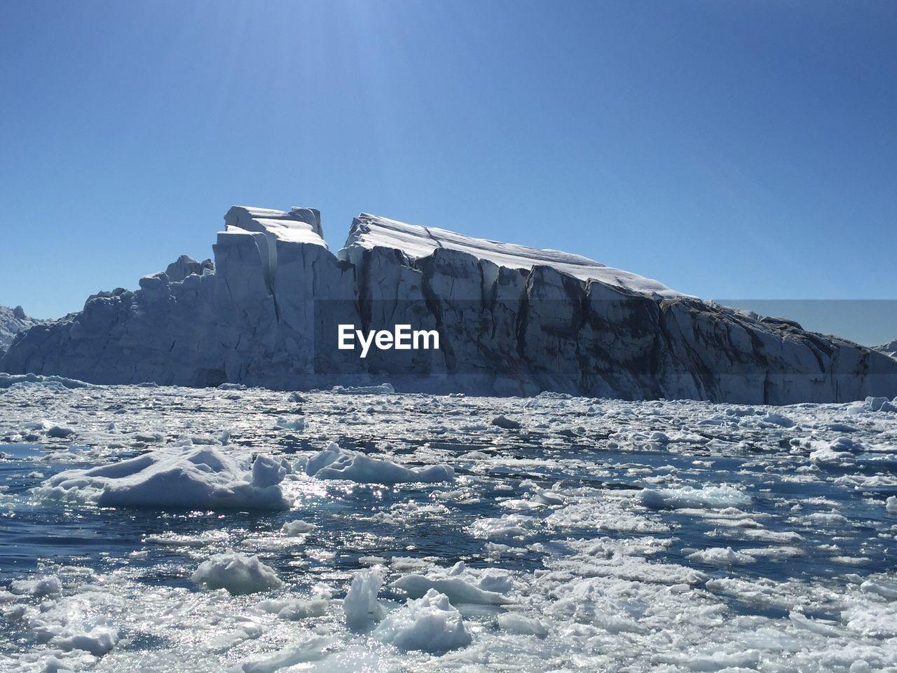 Built Structure On Frozen Landscape Against Clear Blue Sky