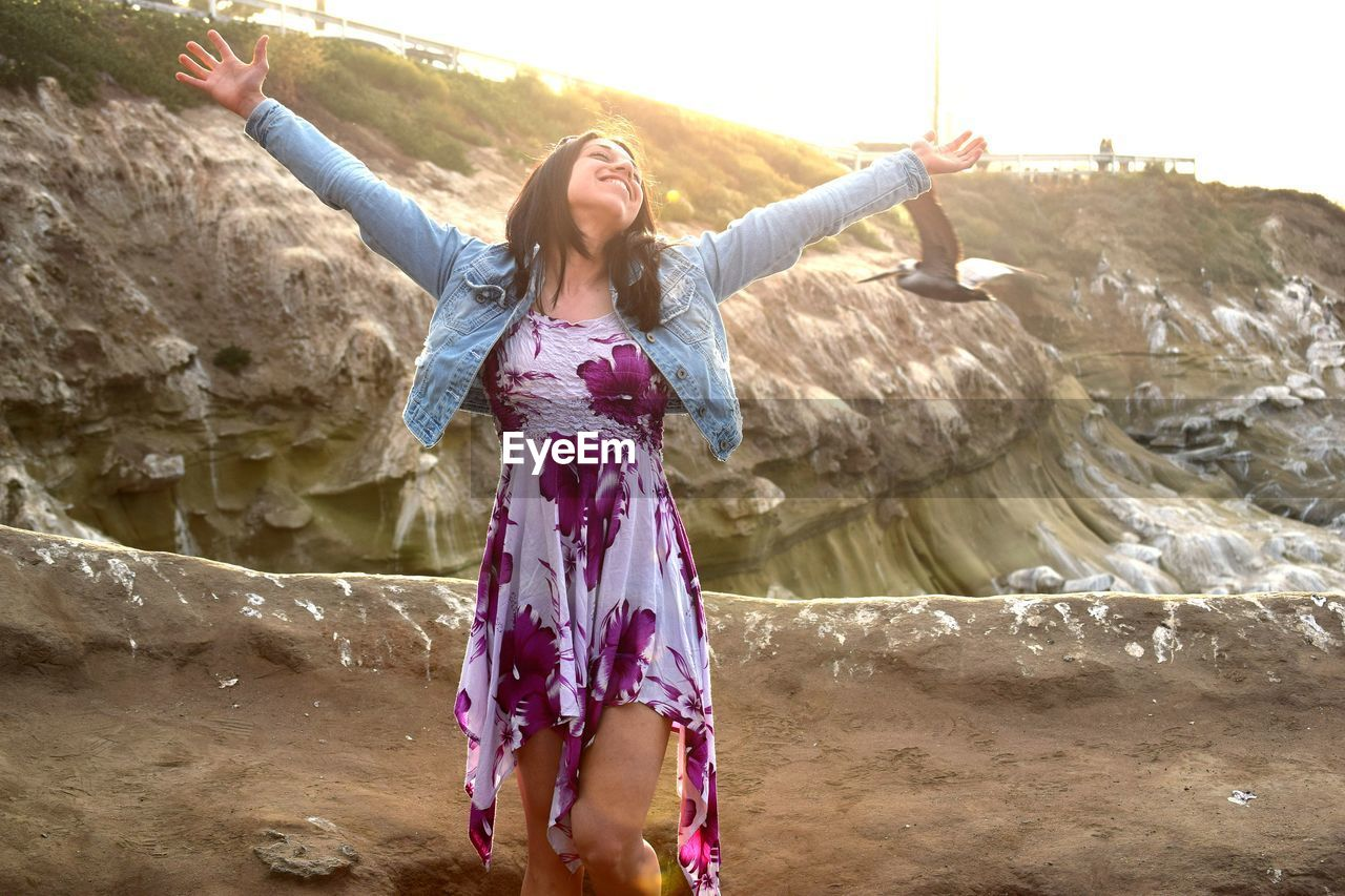 Cheerful Woman With Arms Outstretched Standing Against Rock Formations