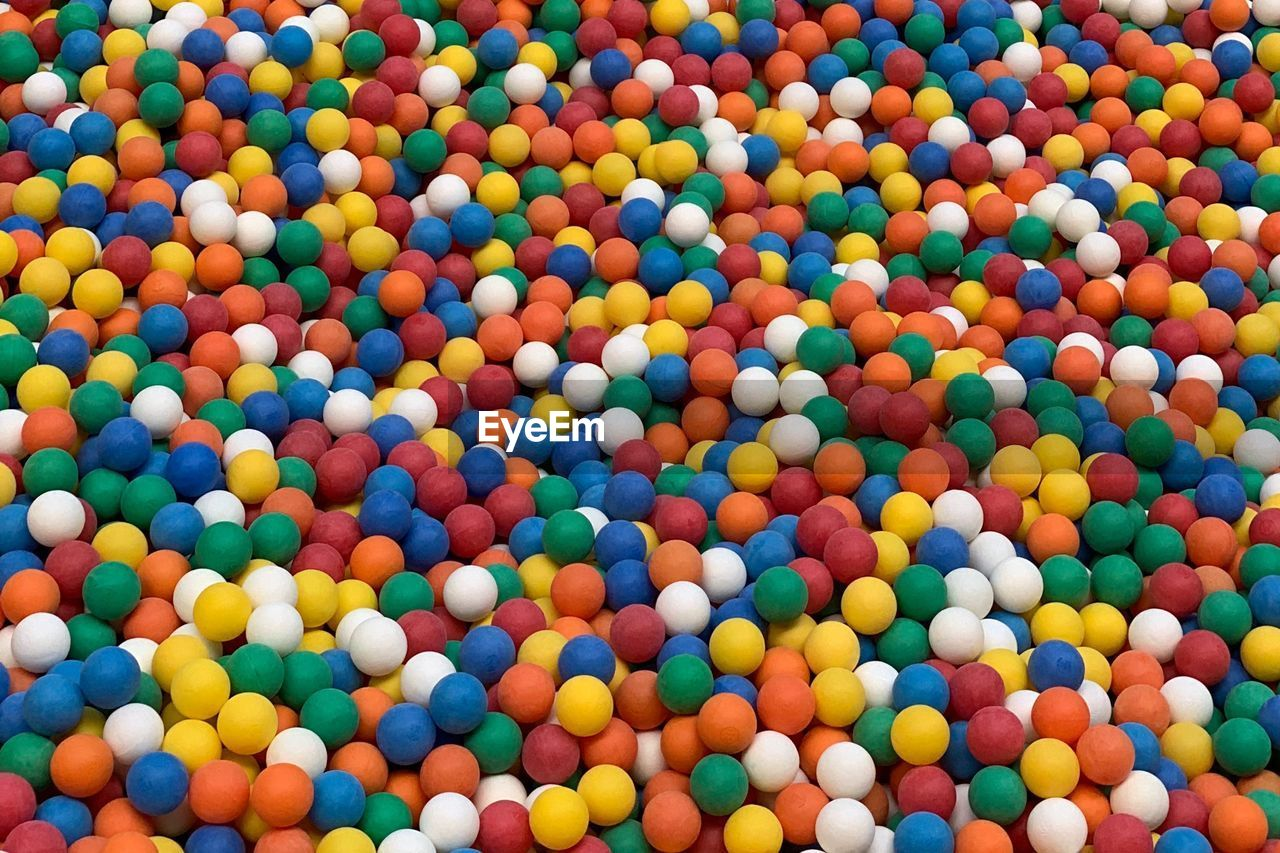 HIGH ANGLE VIEW OF MULTI COLORED BALLS IN CONTAINER