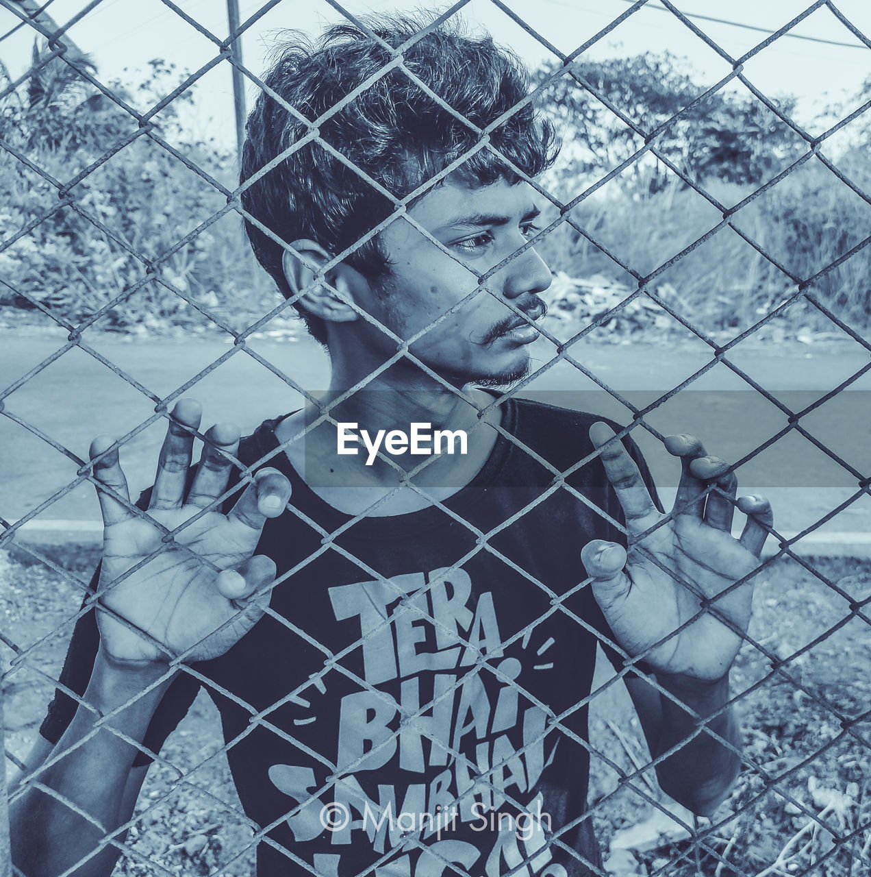 PORTRAIT OF BOY LOOKING THROUGH CHAINLINK FENCE IN WATER