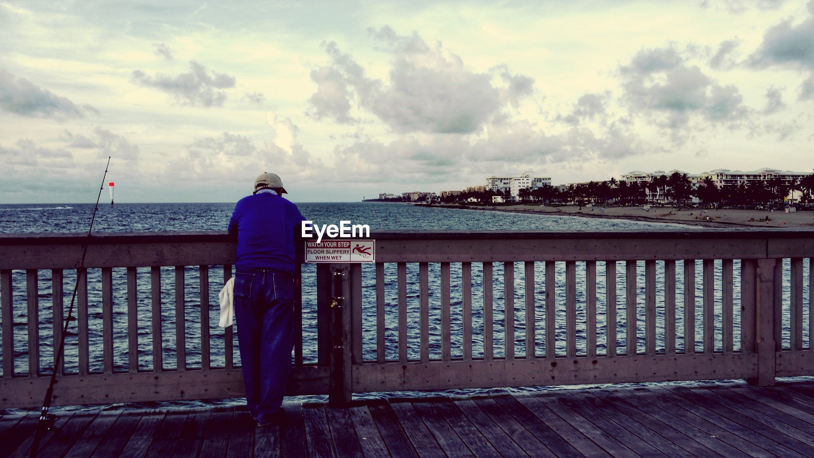 Rear view of man standing on pier over sea against cloudy sky