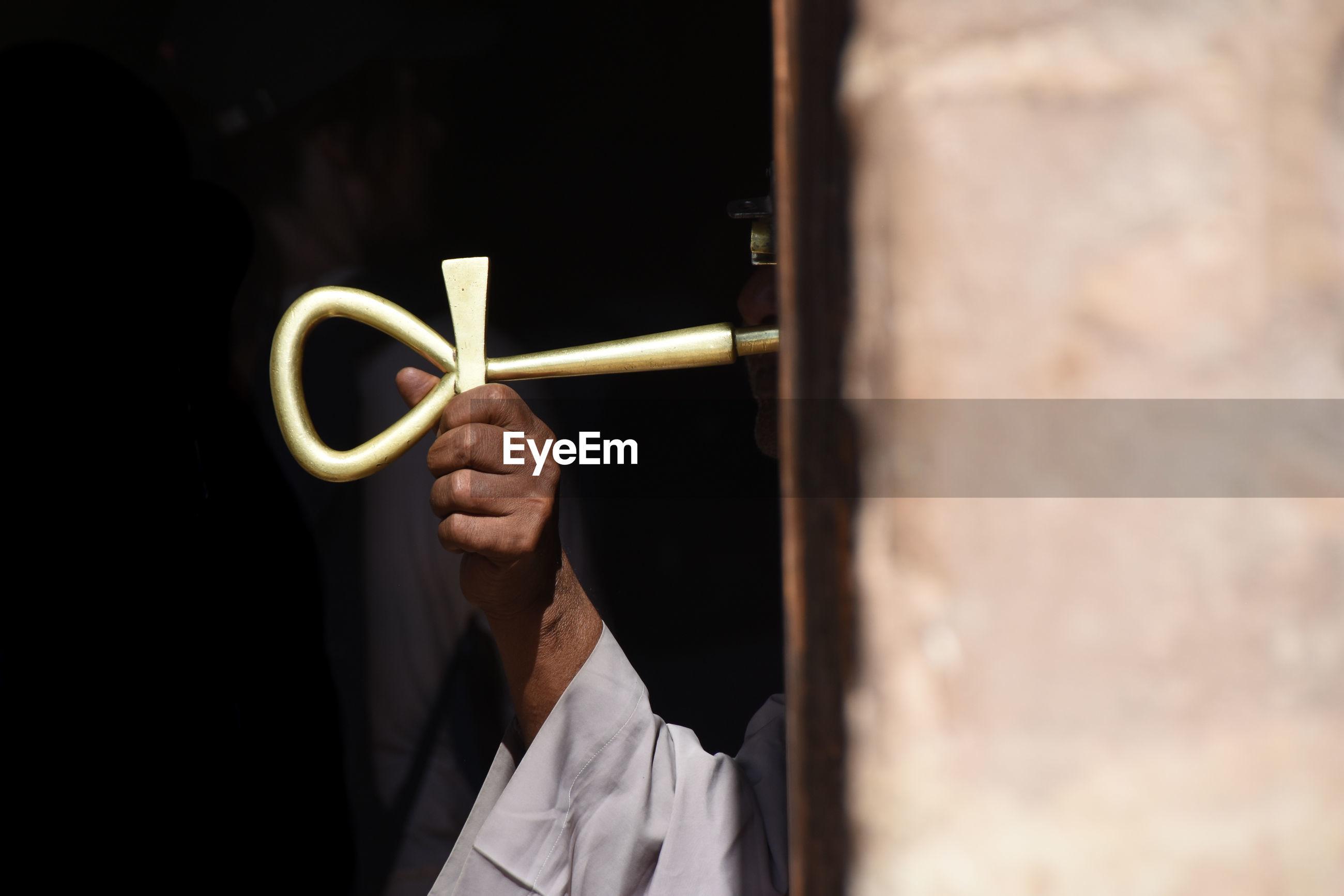 Close-up of man holding golden key