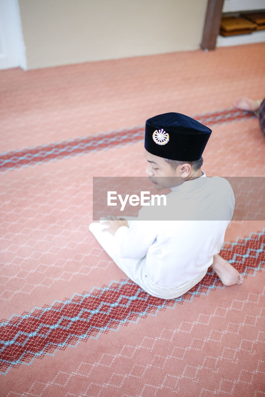 High angle view of man sitting on carpet