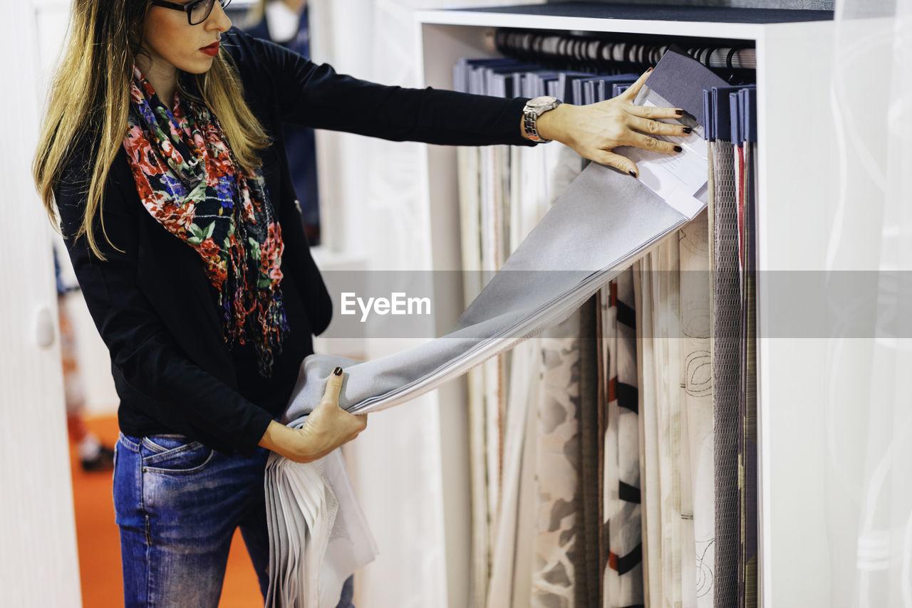 Woman choosing fabric at store