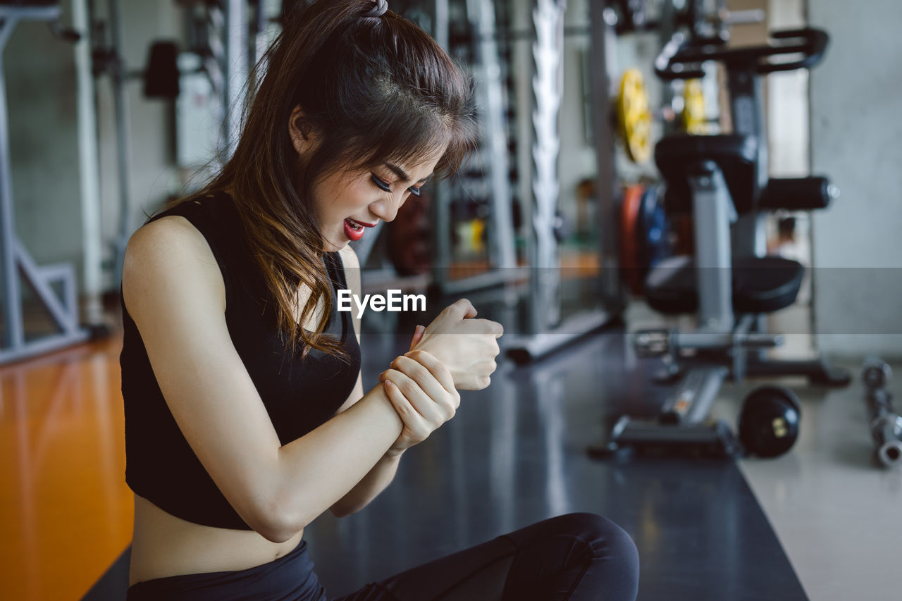 Young Woman Suffering From Joint Pain While Exercising In Gym