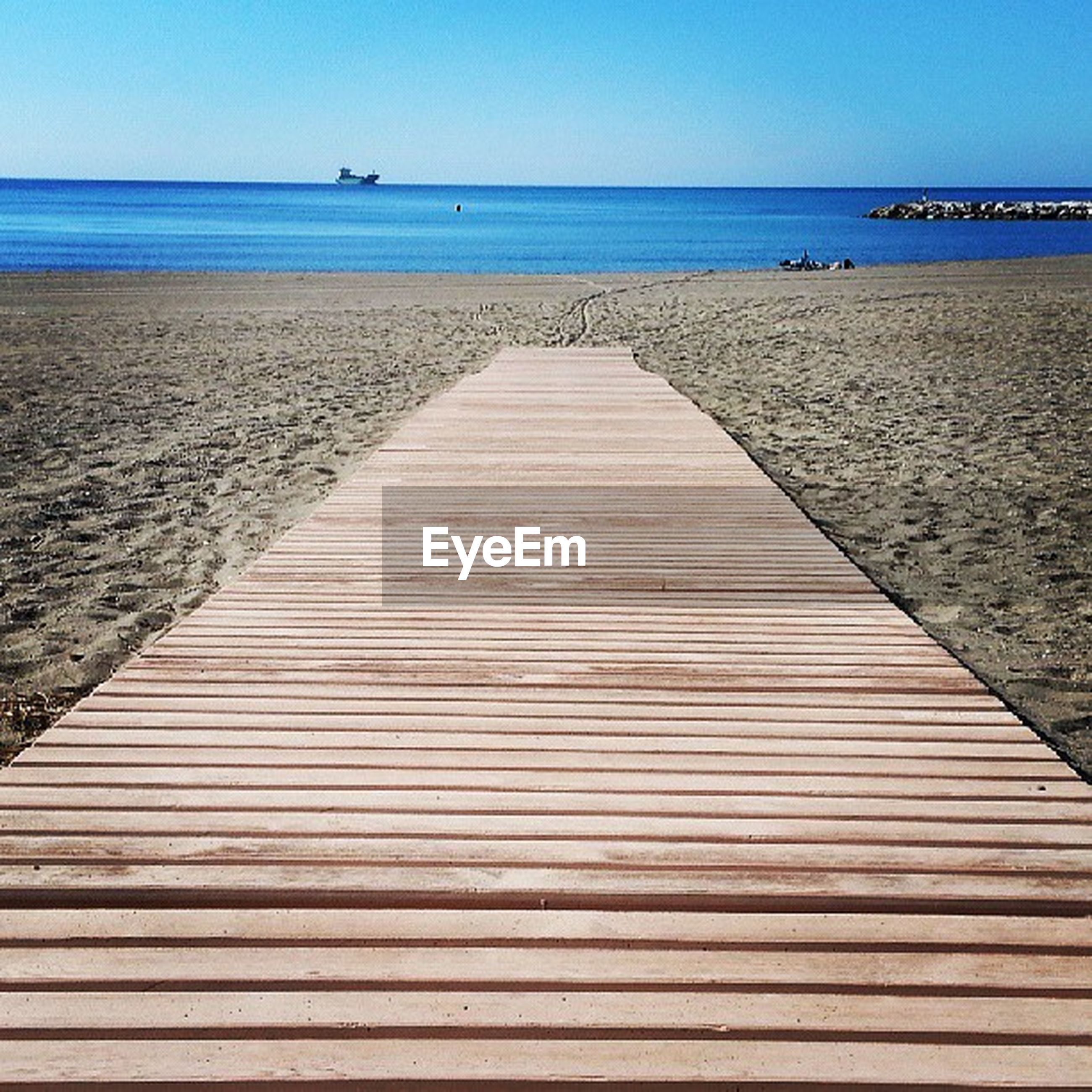 sea, water, horizon over water, beach, tranquil scene, tranquility, clear sky, shore, sand, pier, scenics, blue, the way forward, nature, wood - material, beauty in nature, boardwalk, jetty, sky, incidental people