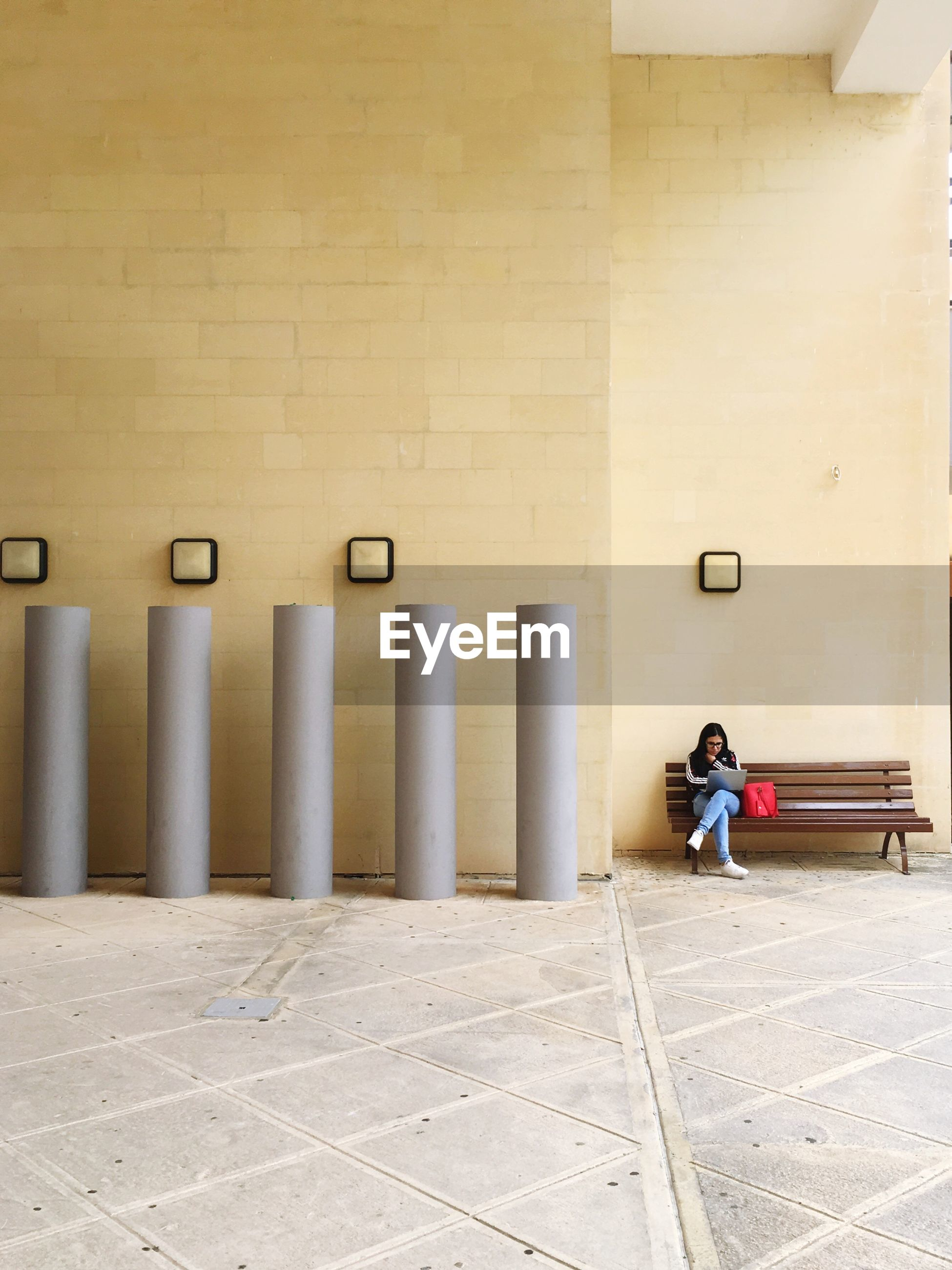 Woman sitting on bench against the wall